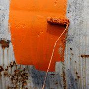 applying orange anti corrosion coating on rusted surface